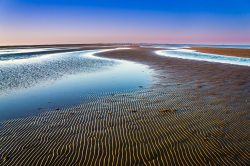 The wave pattern on the sand was softly lit as the sun sets in Bolivar Peninsula in Texas.